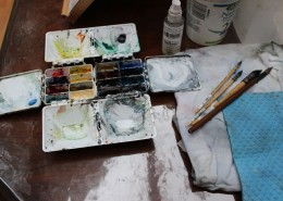 Set of watercolour paints with four paint brushes next to it.