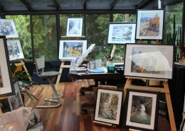 Art studio with paintings on display; windows with a view to trees in the background.