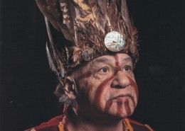 Portrait of a man in traditional regalia including a feathered headdress.