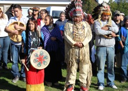 Members of the Mathias family standing together in a park wearing traditional regalia.
