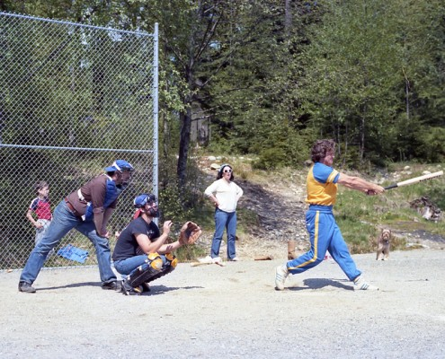 Man in full swing hitting a softball with the catcher and umpire behind him