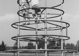 Two young girls at the top of a set of tall monkey bars.