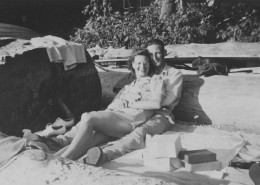 Couple with picnic sitting on a beach next to a large log.