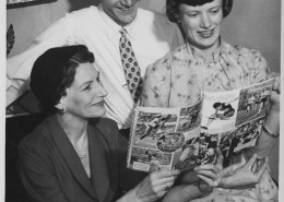 Man with two women looking at a track and field magazine together.
