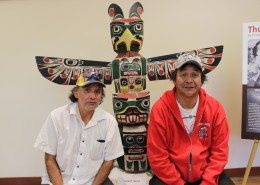Two men sitting in front of a colourful thunderbird totem pole.