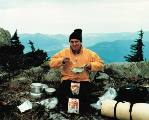 Man siting outdoors eating scrambled eggs from a pan with mountains in the background.