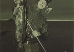 Young man in a wetsuit, holding up a freshly caught fish.