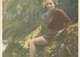 Colorized photo of Yvonne leaning against a large rock next to a stream.