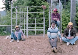 Four men sitting in a playground next to a set of monkey bars, a baseball glove is hanging from the bars.