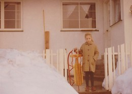Young girl holding a sled, standing on the back steps of her home. Snow is on the ground.