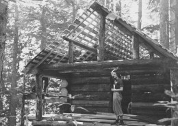 Woman standing on the deck of a cabin under construction. Trees in the background.