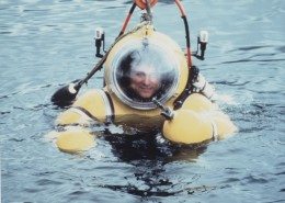 Man partly submerged in water wearing a yellow atmospheric diving suit.