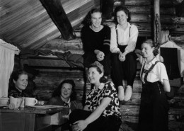 Six smiling young women in a log cabin, two are on a wooden bunk bed.