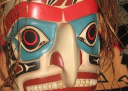 Carved mask in white, blue, black, and red with small shells for teeth and beaten cedar bark for hair.