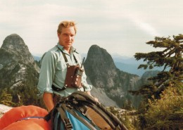Man wearing a chest radio pack with a view of The Lions mountain peaks behind him.