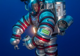 Underwater image of a man in a silver diving suit.