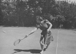 Woman wearing a polka dot dress and swinging a tennis racket.