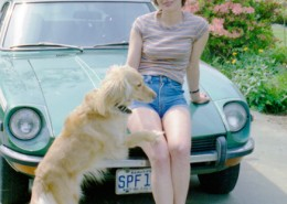 Woman leaning against the hood of her car with a dog jumping up onto her.