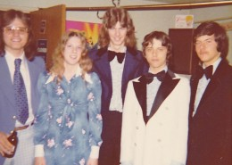 Four young men and one young woman standing together in 1970s formal attire.