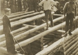 Three man standing on the log frame of a cabin that is under construction.