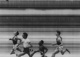 Four male athletes racing for the finish line.