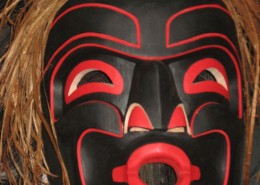 Mask of a human face, mostly black with red accents, and beaten cedar bark for hair.