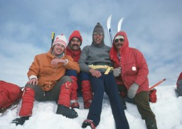Four members of the North Shore Rescue sitting on a snow bank wearing ski gear.