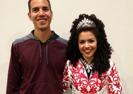 Teenage girl wearing a silver crown and Irish dance costume standing next to her brother.