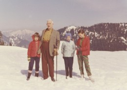 Man with three young girls standing on a snowy landscape, a mountain in the background.