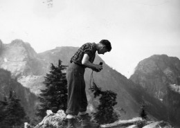 Man holding binoculars with snow-covered mountains behind him.