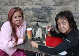 Two women sitting at a table—one of them is holding up a black and white photograph of a relative wearing a headdress.