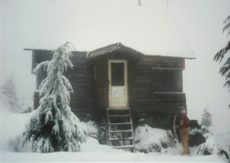 Man standing next to a small wooden cabin covered in snow.