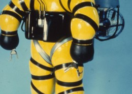 Front view of a yellow atmospheric diving suit.