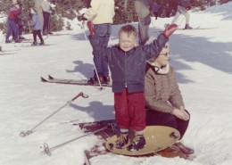 """Woman kneeling next to a boy who is standing on a """"flying saucer"""" sled, his arms up in the air."""