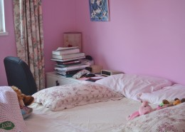 Corner of a bedroom, showing unmade bed, pillows, pink walls, and a stack of books.
