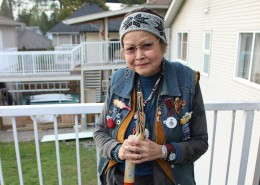 Woman standing on the deck of a house holding a walking stick and wearing traditional beadwork pieces on her jacket.
