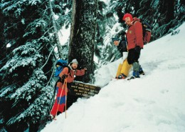 Three members of the NSR on a mountain slope next to sign that reads: If you are lost, wait here for rescue. Do not go down any further.