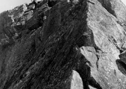 View from below of two men sitting on the rocky ridge of a mountain.