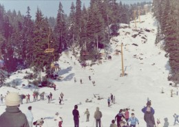 Landscape shot showing ski hill, chair lift, skiers and spectators.