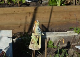 Vintage ceramic bird ornament in a garden.