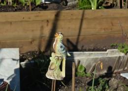 Vintage ceramic bird ornament in a garden.
