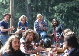 Several men sitting around a picnic table on a deck, trees in the background.