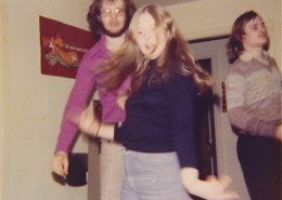Catherine and two men dancing at a party, her long hair is swinging.