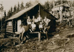 Group of people gathered on the porch of a cabin holding signs, a second cabin can be seen in the distance.