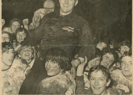 Newspaper clipping with an image of Bill and his team celebrating a football game win.