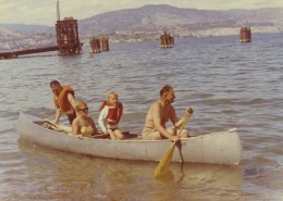 Canoe on a lake with a man paddling, a woman sitting, a child wearing a life preserver, and another man wading next to the canoe.