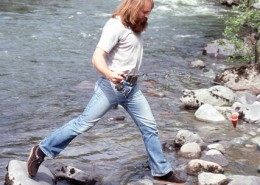 Man with fishing rod stepping from one rock to another in a stream. 5tags: photography, North Vancouver, Lynn Valley, Bruce Flanagan, softball, archives
