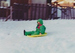 Young boy wearing a snowsuit, sitting on a sled, a smile is on his face.