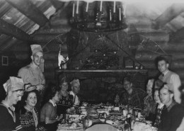 People sitting around a large table celebrating and wearing party hats, a fireplace in the background.