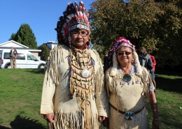 Two people wearing regalia, including headdresses, standing together in a park.